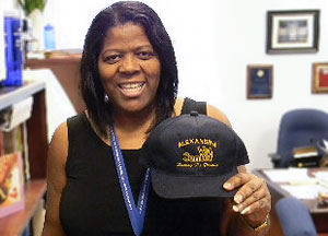 Army Veteran and Alexandria Vet Center Team Leader Alice Ford standing in her office holding a baseball cap with the Vet Center logo.