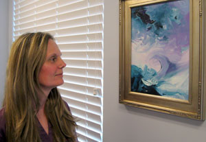 Alexandria Vet Center Counselor Narda Saunders admires a painting presented to her by one of her Veteran clients.