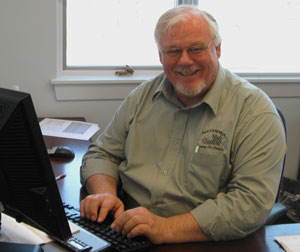 Vet Center Outreach Specialist Hal Koster looks up from his computer to smile for the camera.