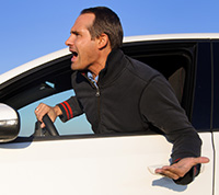 A young man sticks out his top half body from his car window and screams at something.