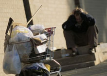 Photo of a homeless man sitting behind a shopping cart full of his possessions.